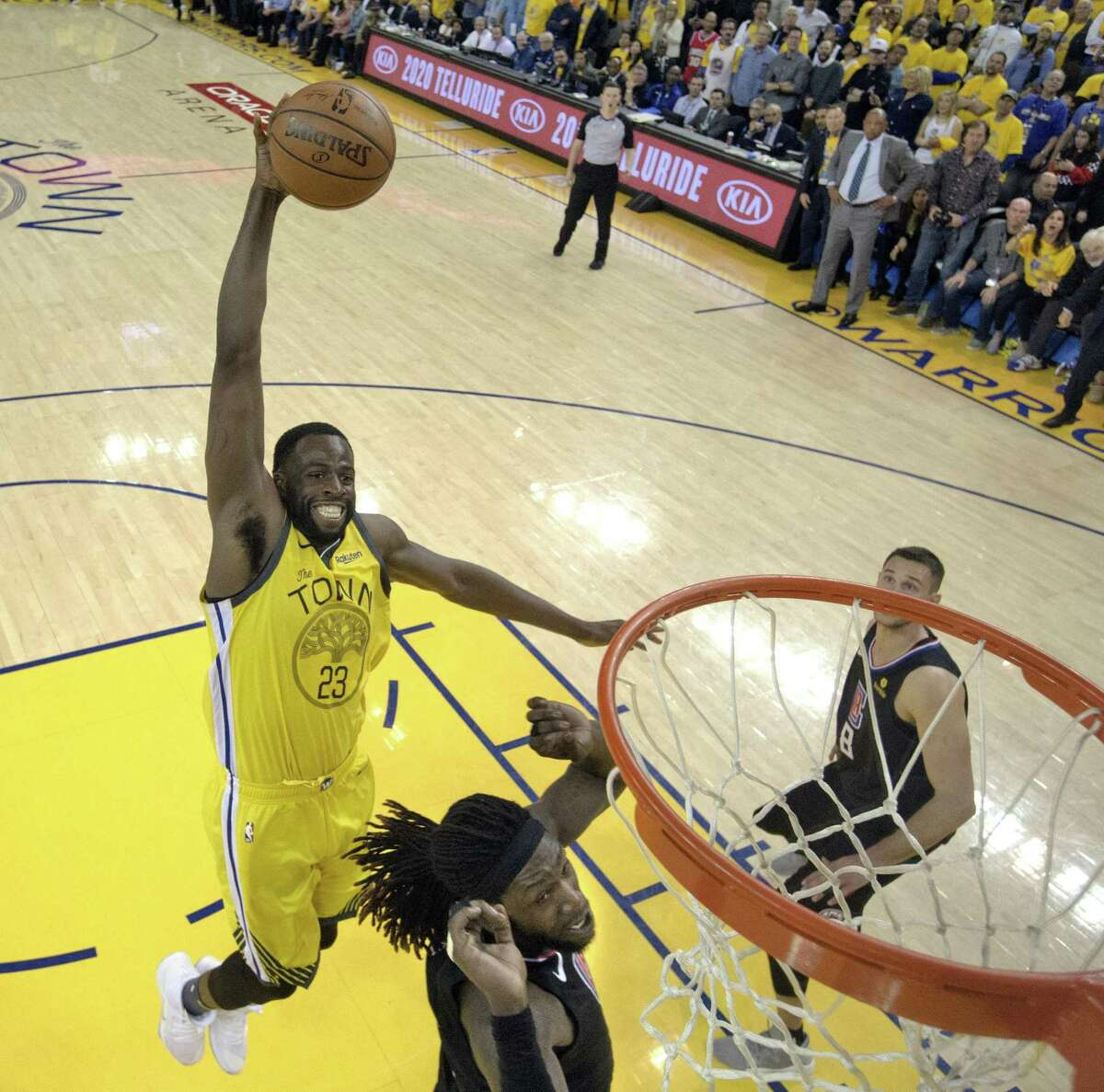 Draymond Green dunks over Montrezl Harrell in the second half as the Golden State Warriors played the Los Angeles Clippers in Game 2 of the First Round of the NBA Playoffs at Oracle Arena on Tuesday, April 16, 2019.
