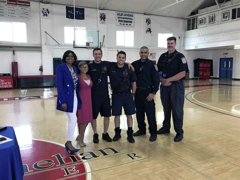 Lorraine Gibbons and Maritza Bond pose with Bridgeport, Conn., firefighters on May 17, 2019, at the graduation ceremony of children who participated in the spring swimming lessons at the Cardinal Sheehan Center. Photo: Hearst Connecticut Media / Tara O'Neill