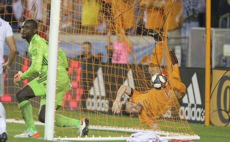 Dynamo midfielder Thomas McNamara scores the go-ahead goal against D.C. United goalkeeper Bill Hamid, left, during the second half at BBVA Compass Stadium on Saturday night.