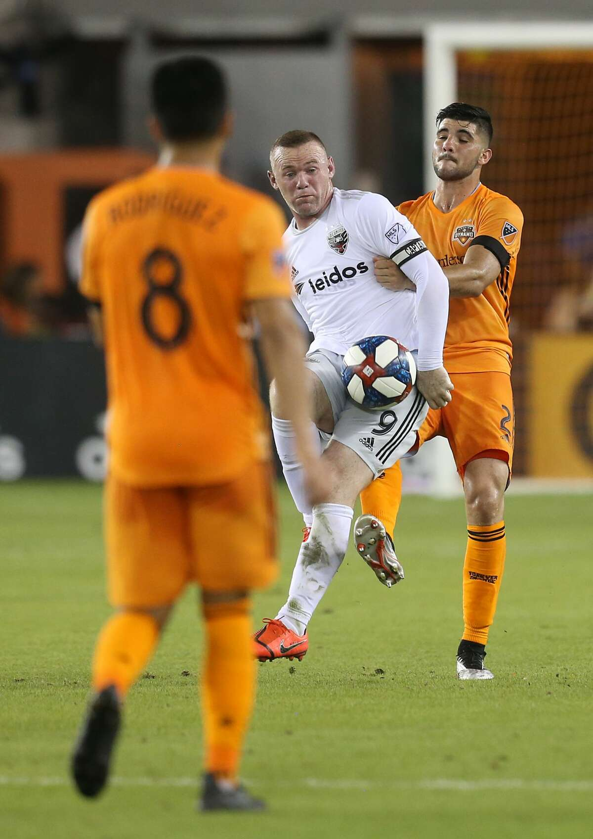 USA: TX: Houston: D.C. United forward Wayne Rooney (9) kicks the ball while being defended by Houston Dynamo defender Alejandro Fuenmayor (2) in the first half on May 18, 2019 at BBVA Compass Stadium in Houston, TX.