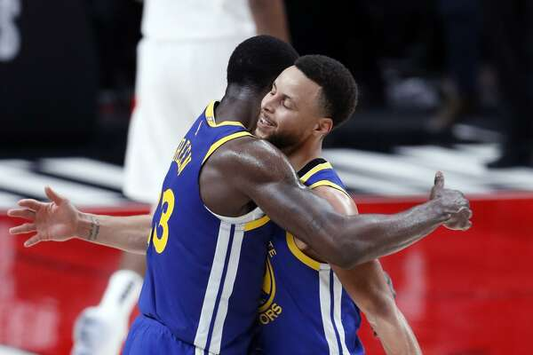 Golden State Warriors' Stephen Curry and Draymond Green embrace at end of Warriors' 110-99 win over Portland Trail Blazers in Game 3 of the NBA Western Conference Finals at Moda Center in Portland, Oregon on Saturday, May 18, 2019.