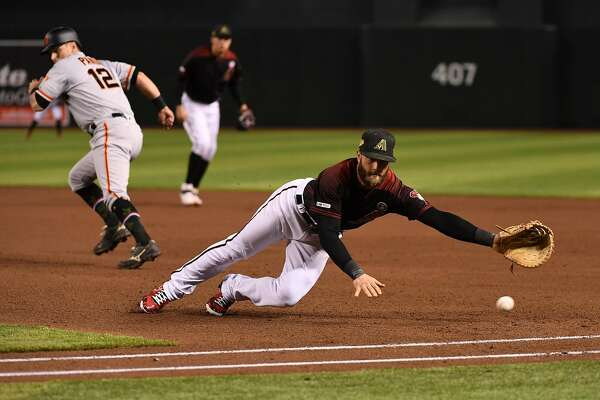 PHOENIX, ARIZONA - MAY 18: Christian Walker #53 of the Arizona Diamondbacks attempts to make a diving stop on a ball hit by Steven Duggar #6 of the San Francisco Giants during the third inning at Chase Field on May 18, 2019 in Phoenix, Arizona. Joe Panik #12 scored on Duggar's triple. (Photo by Norm Hall/Getty Images)