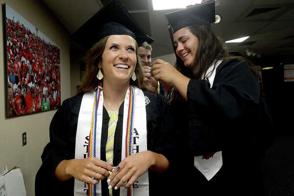 Madeline Myers jokes with Priscilla Garza as she gets help securing her mortar board as Lamar University graduates of the College of Business prepare for the start of their commencement ceremony Saturday at the Montagne Center. Five of the school's colleges held graduation ceremonies this weekend. Photo taken Saturday, May 18, 2019 Kim Brent/The Enterprise