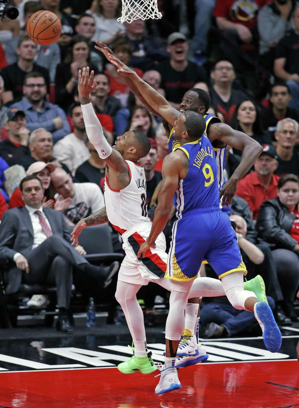 Golden State Warriors' Draymond Green and Andre Iguodala stop Portland Trail Blazers' Damian Lillard on a drive during Warriors' 110-99 win in Game 3 of the NBA Western Conference Finals at Moda Center in Portland, Oregon on Saturday, May 18, 2019.