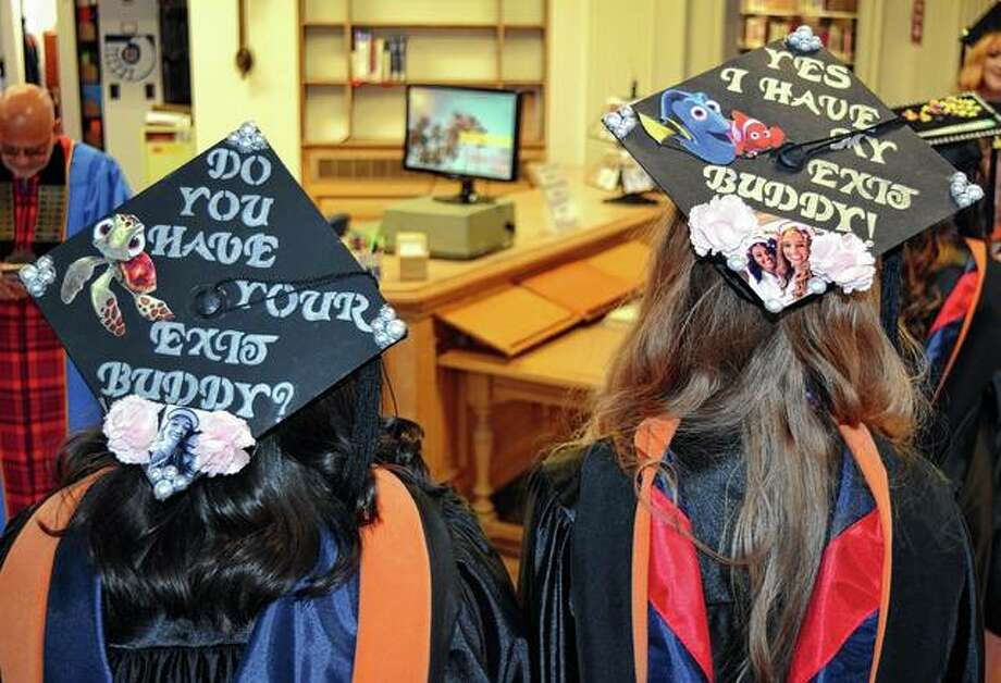 Two MacMurray College graduates decorated their caps for the commencement ceremony Saturday. Photo: Samantha McDaniel-Ogletree | Journal-Courier