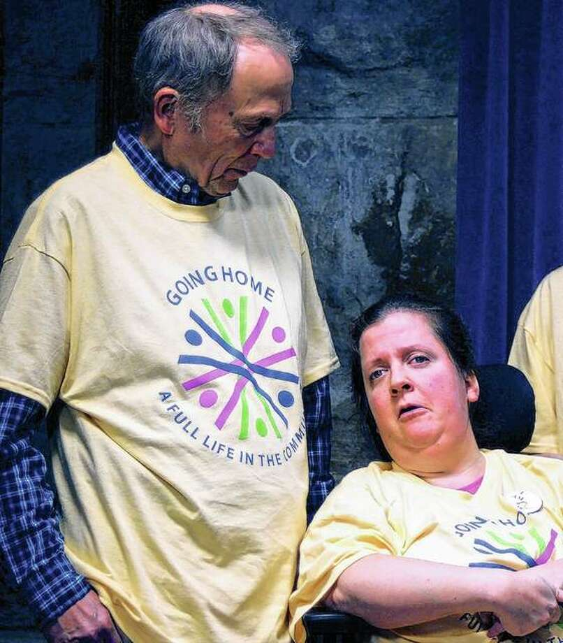 Tony Stahl of DeKalb County looks on as his daughter, Allison, speaks about the eight-year wait it took to get into a community home, where she now lives and pays rent with two other roommates. The Stahls were at the Capitol in Springfield this week to advocate for increased state funding to move people with disabilities from state institutions to community homes. Photo: Grant Morgan | Capitol News Illinois