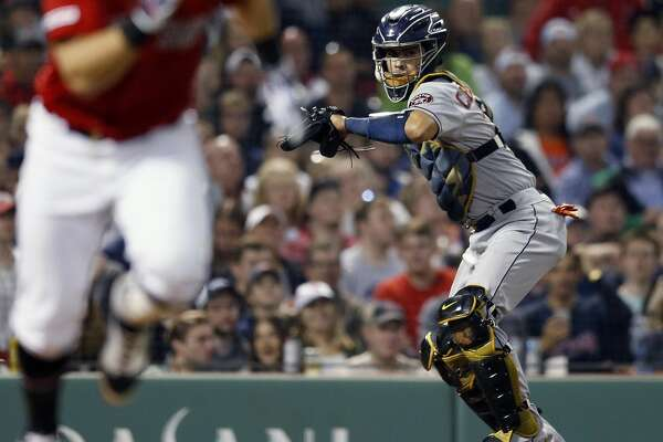 Boston Red Sox's Michael Chavis, left, runs on his third strike as Houston Astros' Robinson Chirinos throws to first base during the sixth inning of a baseball game in Boston, Friday, May 17, 2019. (AP Photo/Michael Dwyer)