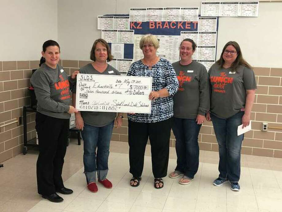 Members of the School Lunch Debt Solutions Team present a $7,000 check to the Edwardsville District 7 School Board. Pictured are Sheri Ammon, Lynette Watson, School Board President Jill Bertels, Heather Porter and Trish Oberweis. Not pictured are Tori Siron and Betsy Ward. Photo: Julia Biggs | The Intelligencer