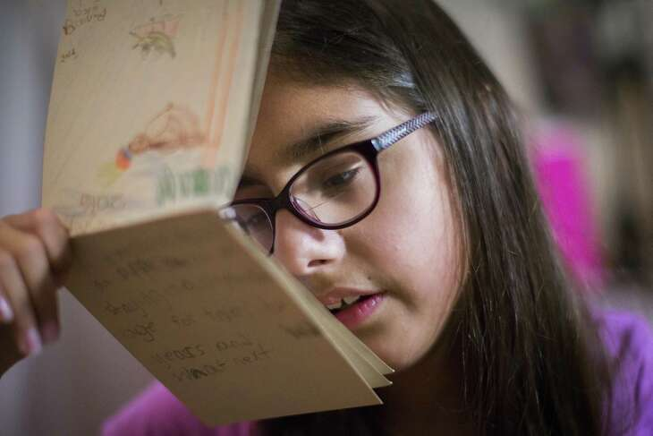 Sophia Salehi, 9, gets close to read an illustrated story she wrote and illustrated about a talking banana, Saturday, Dec. 17, 2016, in her home in Pearland. Salehi was born prematurely and is a surviving twin. She is also legally blind but she was denied special education services by Houston Independent School District. ( Marie D. De Jesus / Houston Chronicle )