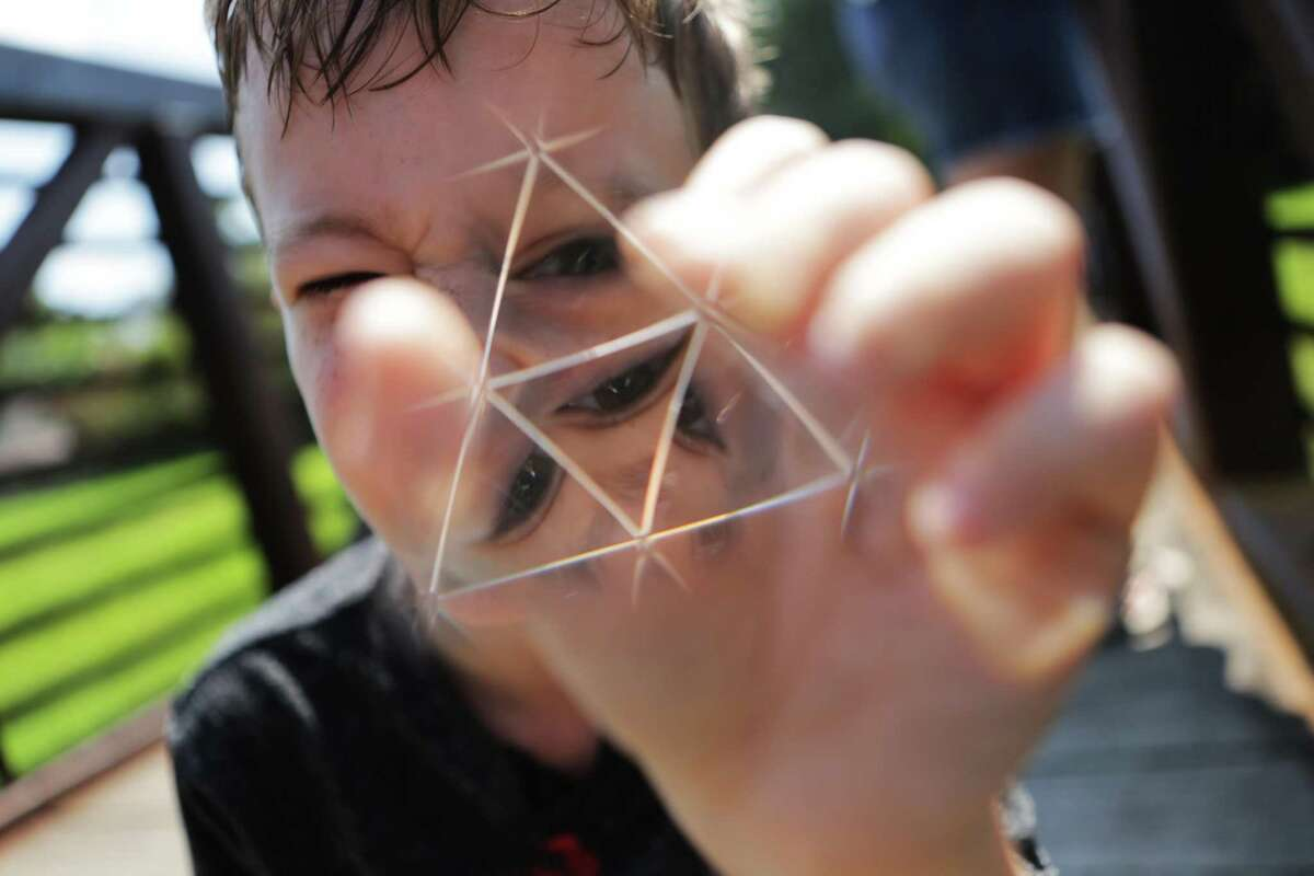Roanin Walker's gaze disperses through the forms of a prism in face of the light on Friday, Sept. 2, 2016, in Kingwood. Walker finds comfort in science, maths and facts. He was homeschooled by his mother after been denied special education. Roanin was diagnosed with attention deficit disorder, anxiety and sensory processing disorder. ( Marie D. De Jesus / Houston Chronicle )