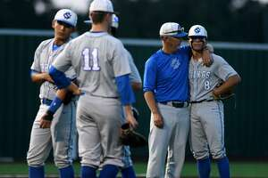 Clear Springs baseball coach Chris Floyd (center) consoles Chargers starting pitcher Mason Schulz (8) after a rough outing against Atascocita in their Region III-6A quarterfinal series matchup.