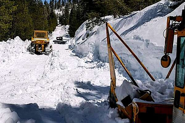 Snow plow crews work to clear Tioga Road/Highway 120 near Siesta Lake at about 8,000 feet in Yosemite National Park