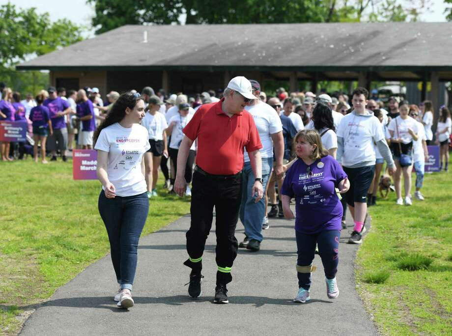 Stamford Mayor David Martin walks with Epilepsy Foundation of Connecticut Teen Ambassador Emma Borys, left, and motivational speaker Beth Usher, who had the left hemisphere of her brain removed to treat her seizures, at the Walk to End Epilepsy at Cove Island Park in Stamford, Conn. Sunday, May 19, 2019. About 200 walkers and 50 cyclists participated to support epilepsy awareness and raise money for the Epilepsy Foundation of Connecticut. The Stamford walk was the last in the series of walks in Connecticut and the group is very close to reaching its target goal of raising $100,000. Photo: Tyler Sizemore / Hearst Connecticut Media / Greenwich Time