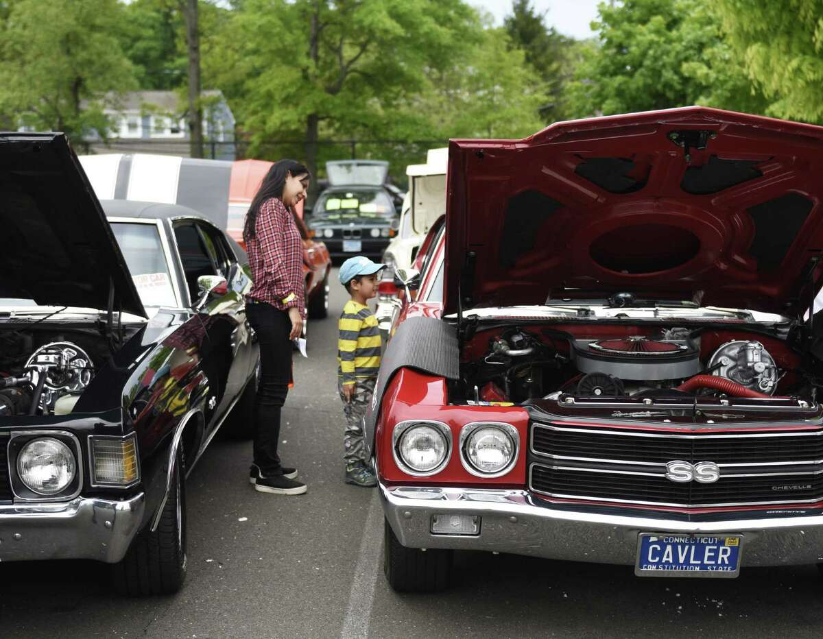 Stamford's Anoop Kaur and Evaan Ahmed, 4, look at a Chevrolet Chevelle at JM Wright Technical School's Car and Motorcycle Show Fundraiser at Scalzi Park in Stamford, Conn. Sunday, May 19, 2019. Dozens of old and new cars, as well as motorcycles, were on display at the event. Sarah Edwards, the former driver of Queen of Diamonds II jet dragster, was the show's guest of honor. Proceeds benefited the JMWT PFO for shop materials, field trips, after-school activities, scholarships, post-graduation parties and proms.