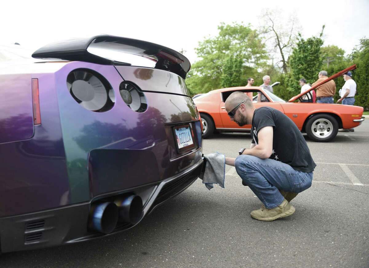 Wallingford's Richard Pierce shines up his 2016 Nissan GT-R at JM Wright Technical School's Car and Motorcycle Show Fundraiser at Scalzi Park in Stamford, Conn. Sunday, May 19, 2019. Dozens of old and new cars, as well as motorcycles, were on display at the event. Sarah Edwards, the former driver of Queen of Diamonds II jet dragster, was the show's guest of honor. Proceeds benefited the JMWT PFO for shop materials, field trips, after-school activities, scholarships, post-graduation parties and proms.