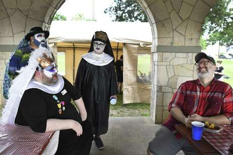 Novice Sister Minerva des People, seated at left, gets a laugh from Matt Darke as Sister Skharlott de la Noche, rear left, and Sister Eliza watch during Just One Night, a fundraiser to help San Antonio's homeless youth that was held Saturday evening at Maverick Park. The event was sponsored by nonprofit called San Antonio Sisters of Perpetual Indulgence. Members wear nun habits and face paint to draw the public's attention to their causes. The three members didn't provide their real names.