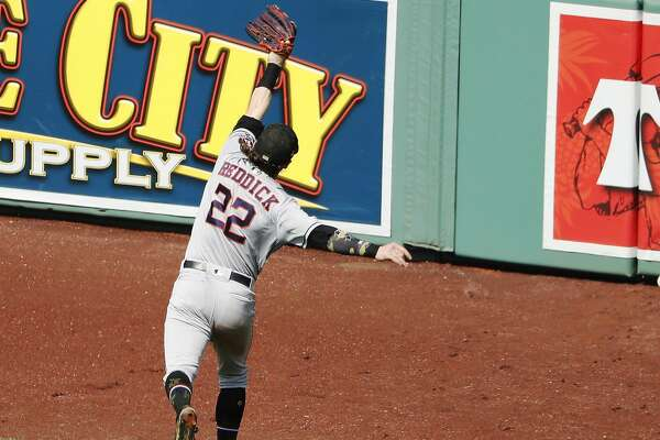 Houston Astros right fielder Josh Reddick leaps but can't get to a double by Boston Red Sox's Mookie Betts during the fifth inning of a baseball game Sunday, May 19, 2019, at Fenway Park in Boston. (AP Photo/Winslow Townson)
