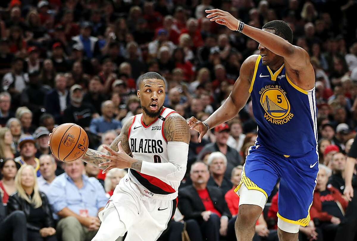 PORTLAND, OREGON - MAY 18: Damian Lillard #0 of the Portland Trail Blazers handles the ball against Kevon Looney #5 of the Golden State Warriors in game three of the NBA Western Conference Finals at Moda Center on May 18, 2019 in Portland, Oregon. NOTE TO USER: User expressly acknowledges and agrees that, by downloading and or using this photograph, User is consenting to the terms and conditions of the Getty Images License Agreement. (Photo by Jonathan Ferrey/Getty Images)