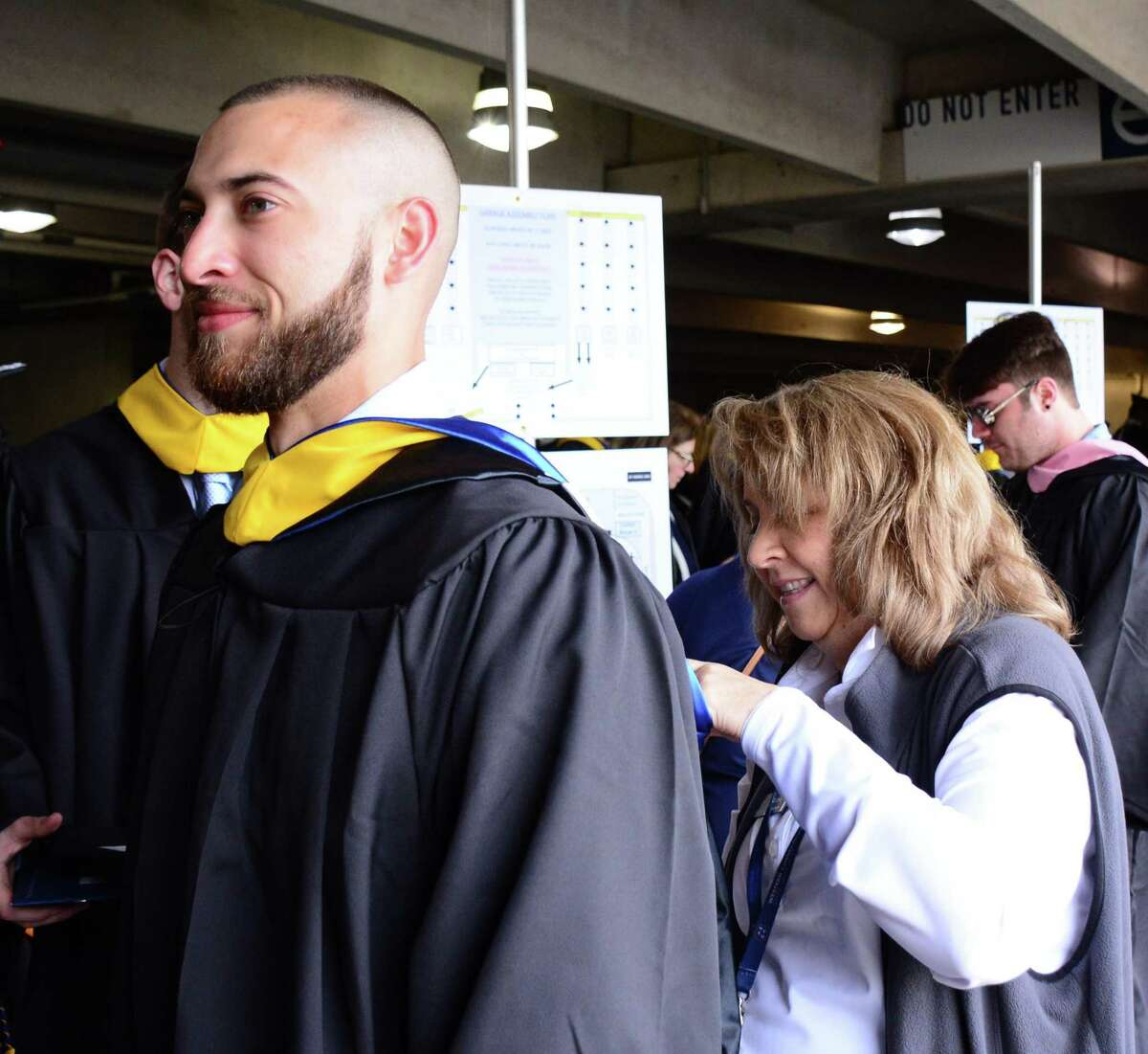 Nancy Barton helps Zachary Lopez with his cap and gown during Western Connecticut State Universities commencement ceremony on Sunday May 19, 2019 at t1he Webster Bank Arena in Bridgeport Connecticut.