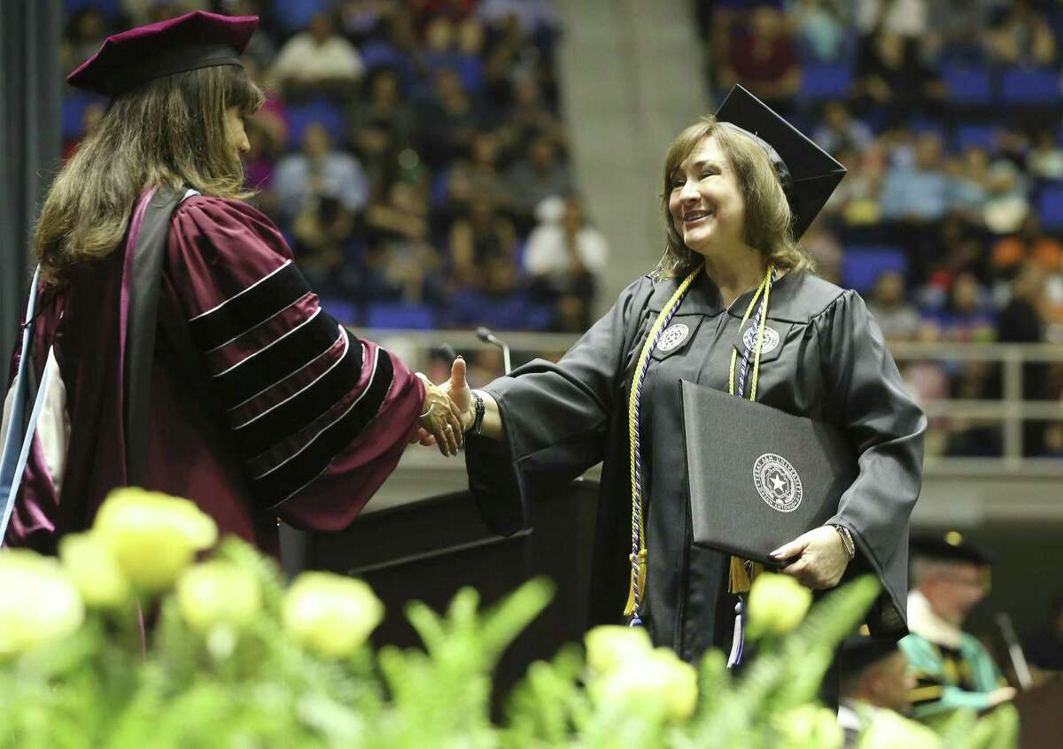 Joyce Raposo (right) walks across the stage to shake hands with Texas A&M University - San Antonio President Cynthia Teniente-Matson during commencement ceremonies on Friday, May 17, 2019. The university is celebrating its 10th year.