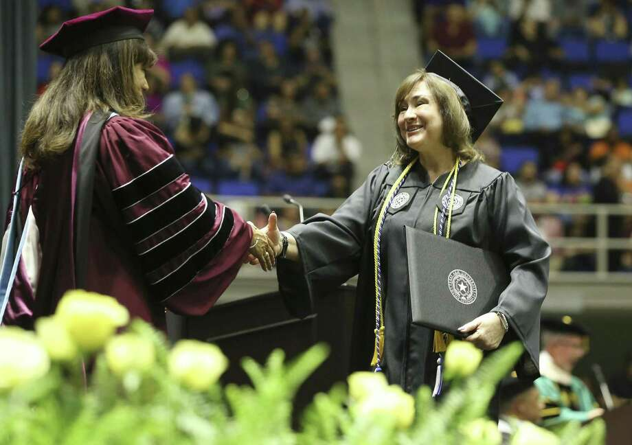 Joyce Raposo (right) walks across the stage to shake hands with Texas A&M University - San Antonio President Cynthia Teniente-Matson during commencement ceremonies on Friday, May 17, 2019. The university is celebrating its 10th year. Photo: Kin Man Hui /Staff Photographer / ©2019 San Antonio Express-News