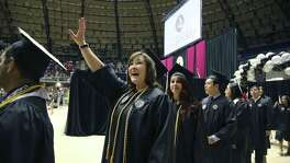 Joyce Raposo waves to family members as she enters the Freeman Coliseum for commencement ceremonies Friday.