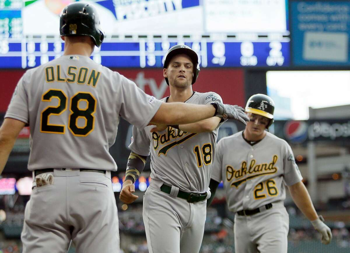 DETROIT, MI - MAY 19: Matt Olson #28 of the Oakland Athletics greets Chad Pinder #18 and Matt Chapman #26 after they scored against the Detroit Tigers on a double by Stephen Piscotty during the seventh inning at Comerica Park on May 19, 2019 in Detroit, Michigan. (Photo by Duane Burleson/Getty Images)