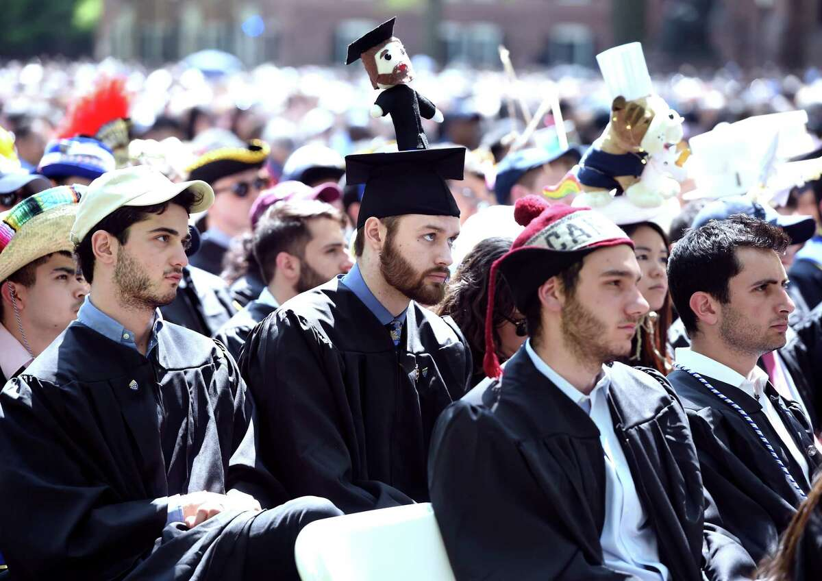 Andrew Moran (center) of Branford College wears a hat decorated with a doll in his likeness for Class Day at Yale University in New Haven on May 19, 2019.