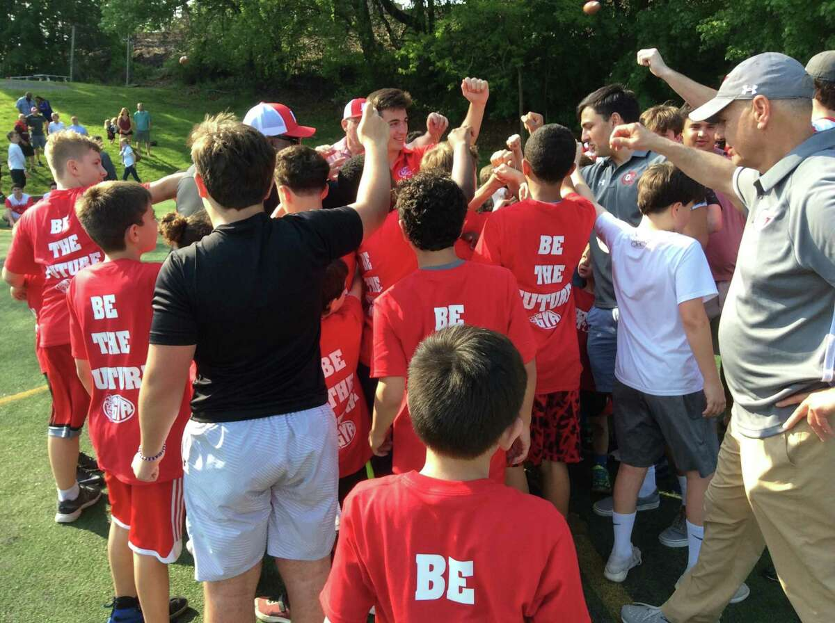 A group of youngsters huddle during a clinic run by the players and coaches of the 2018 Greenwich High School football team on Sunday, May 19, 2019, at the Boys & Girls Club of Greenwich.