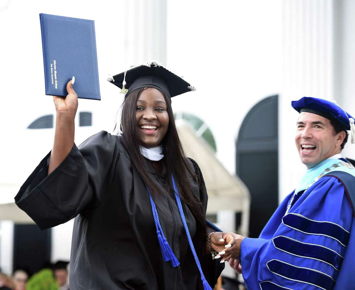 Khyale Johnson (left) shows off the degree she was presented by Albertus Magnus College president Marc Camille (right) during commencement in New Haven on May 19, 2019.