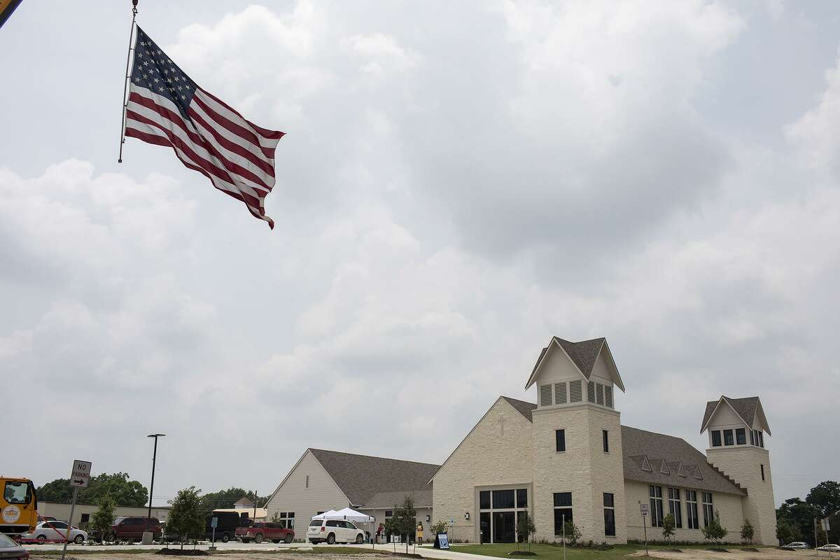 A flag flies from a crane next to the new building for First Baptist Church of Sutherland Springs after the building dedication ceremony Sunday.