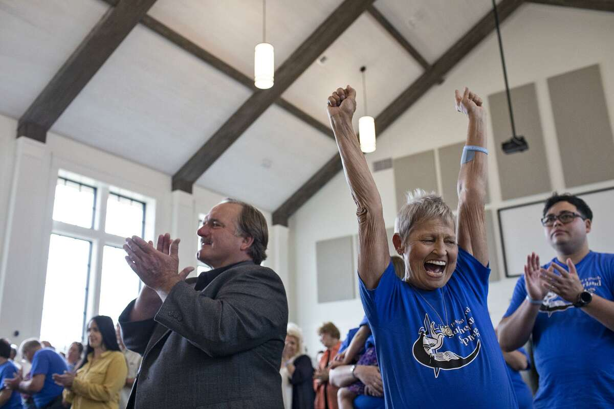 Shooting survivor David Colbath and church member Pam Hollingworth rejoice Sunday as the praise team fills the new sanctuary with music during the private service for church members, survivors and victims' families, the first service held in the new building for First Baptist Church of Sutherland Springs.
