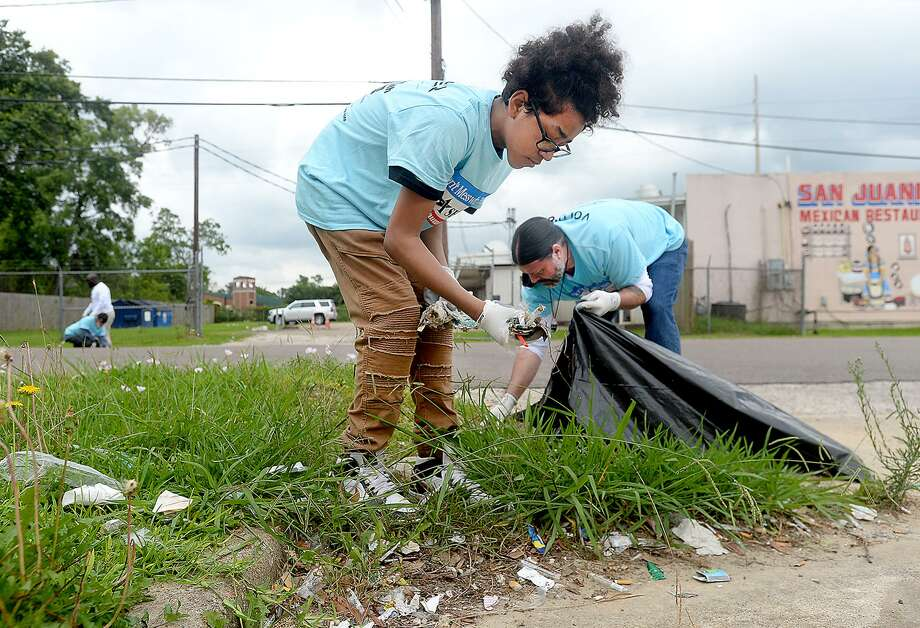 David and his father William Sames help remove trash and other debris in the neighborhood near the John Paul Davis Community Center during Saturday's city-wide Trash Off 2019. Volunteers were stationed in areas throughout the city identified by code enforcement officials as areas in need of clean-up. Photo taken Saturday, May 18, 2019 Kim Brent/The Enterprise Photo: Kim Brent / The Enterprise / BEN