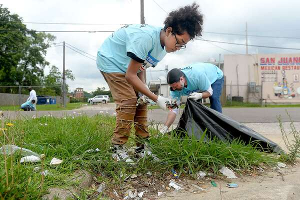David and his father William Sames help remove trash and other debris in the neighborhood near the John Paul Davis Community Center during Saturday's city-wide Trash Off 2019. Volunteers were stationed in areas throughout the city identified by code enforcement officials as areas in need of clean-up. Photo taken Saturday, May 18, 2019 Kim Brent/The Enterprise