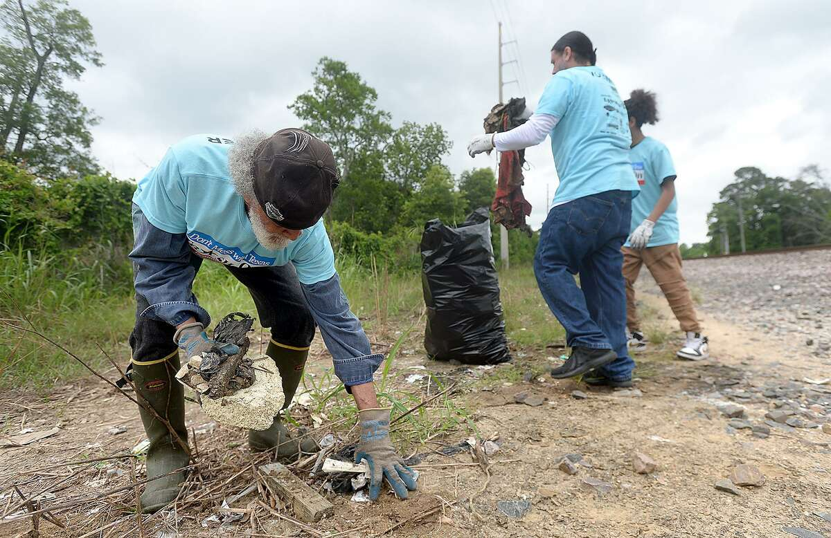 From left, Floyd Guidry and William and David Sames help remove trash and other debris in the neighborhood near the John Paul Davis Community Center during Saturday's city-wide Trash Off 2019. Volunteers were stationed in areas throughout the city identified by code enforcement officials as areas in need of clean-up. Photo taken Saturday, May 18, 2019 Kim Brent/The Enterprise
