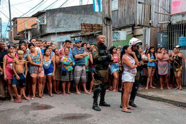 Residents gather outside a bar as forensic personnel and criminal police remove corpses after a shooting, in Belem, Para state, Brazil on May 19, 2019. - At least 11 people were shot dead Sunday at a bar in northern Brazil when unknown men opened fire, Para state Public Security Secretariat informed. (Photo by Mauro ANGELO / Agencia Panamazonica / AFP)MAURO ANGELO/AFP/Getty Images