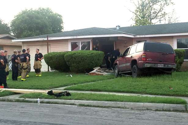 An SUV sits in a yard Sunday evening after crashing into a house on the East Side.