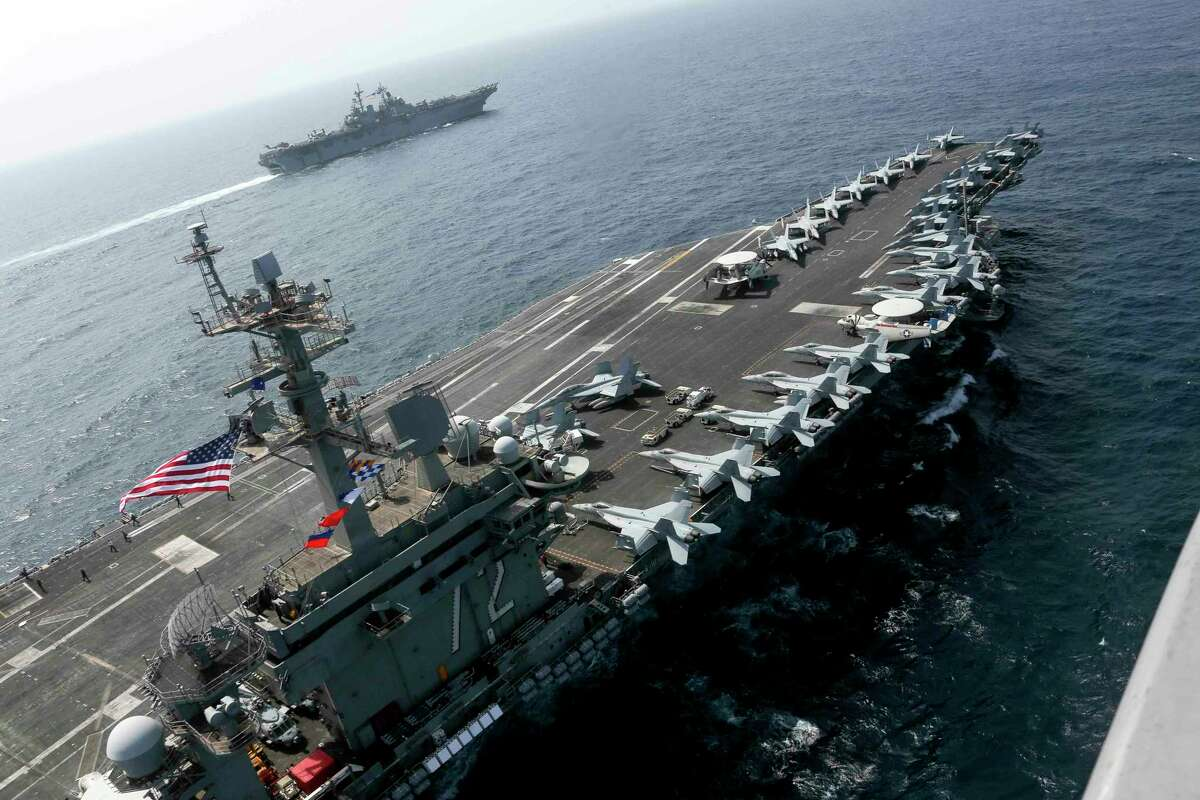 CORRECTS DATE - In this Friday, May 17, 2019, photo released by the U.S. Navy, the USS Abraham Lincoln sails in the Arabian Sea near the amphibious assault ship USS Kearsarge. Commercial airliners flying over the Persian Gulf risk being targeted by