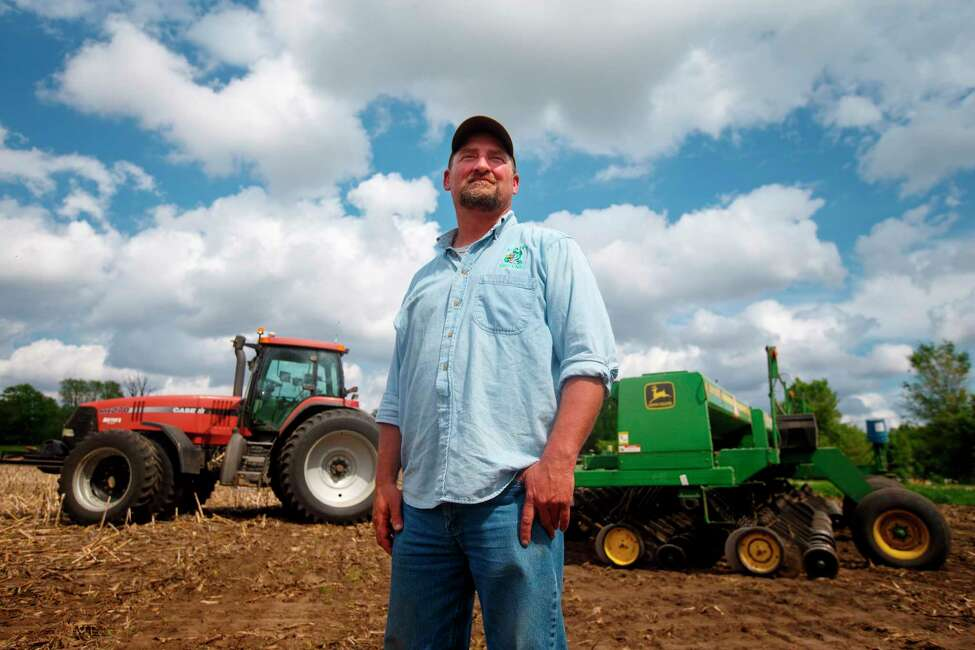 In this May 22, 2019, photo, farmer Tim Bardole pauses for a photo as he plants a field near Perry, Iowa. Donald Trump won the presidency by winning rural America, in part by pledging to use his business savvy and tough negotiating skills to take on China and put an end to trade practices that have hurt farmers for years. While the prolonged fight has been devastating to an already-struggling agriculture industry, there?s little indication Trump is paying a political price. (Zach Boyden-Holmes/The Des Moines Register via AP)