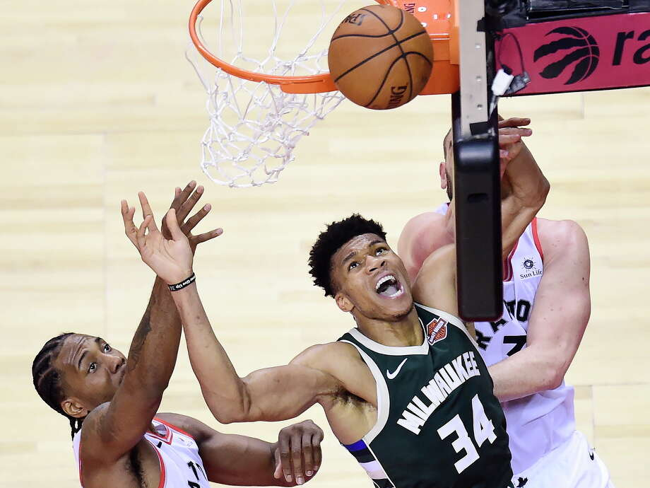 Milwaukee Bucks forward Giannis Antetokounmpo (34) misses a basket under pressure from Toronto Raptors forward Kawhi Leonard, left, and center Marc Gasol,  back right, during the second half of Game 3 of the NBA basketball playoffs Eastern Conference finals in Toronto, Sunday, May 19, 2019. (Frank Gunn/The Canadian Press via AP) Photo: Frank Gunn / The Canadian Press