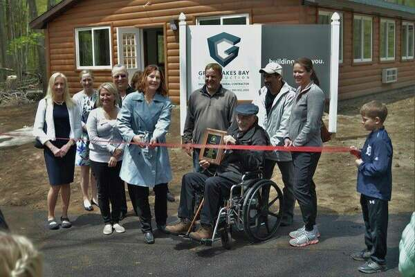 Jenee Velasquez, executive director of The Herbert H. and Grace A. Dow Foundation, cuts a ribbon during a ceremony for a new 24-bed cabin at Camp Fish Tales in Pinconning. She stands among board members, donors and other stakeholders at the camp for people with disabilities. (Ashley Schafer/ashley.schafer@hearstnp.com)