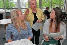 Alexia Ginter (left) and Olivia Hanson (right) speak with Clairice Hetzler before a Teen Court trial at Quincy University in Quincy. The program is set up for first-time, non-violent youth offenders.