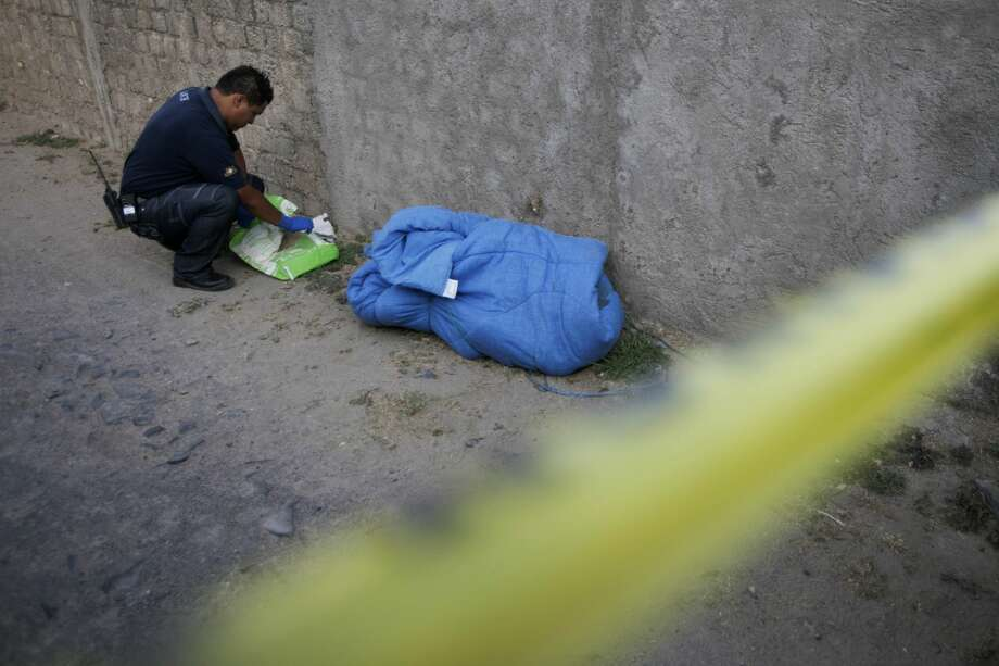 FILE - A forensic works next to the allegedly mutilated body of a drug gang member wrapped in a blanket  after it was found in Tlajomulco on the outskirts of Guadalajara, Mexico, Friday, May 28, 2010. Mexican authorities have found 18 plastic bags and vessels containing human remains in the crime-ridden part of the country, prosecutors said Friday. Photo: Carlos Jasso/ASSOCIATED PRESS
