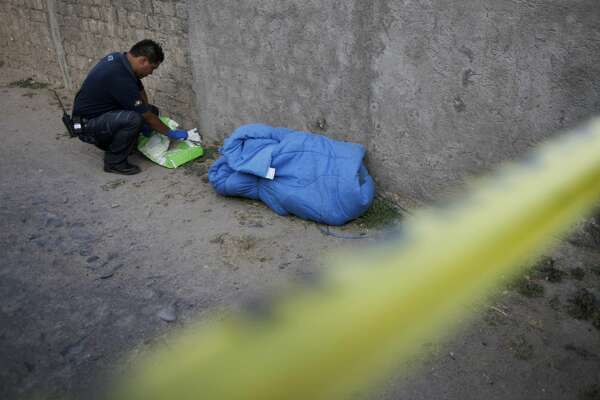 FILE - A forensic works next to the allegedly mutilated body of a drug gang member wrapped in a blanket after it was found in Tlajomulco on the outskirts of Guadalajara, Mexico, Friday, May 28, 2010. Mexican authorities have found 18 plastic bags and vessels containing human remains in the crime-ridden part of the country, prosecutors said Friday.