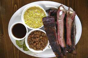 A half-rack plate of pork ribs includes six pork spare ribs with sides of creamed corn and pinto beans at B&B Smokehouse.