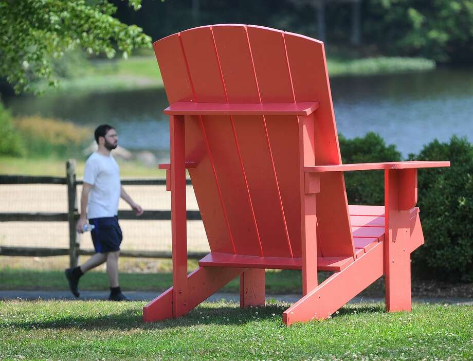 An enormous pink adirondack chair sits by the walking path around Great Hollow Lake in Wolfe Park in Monroe, Conn. The Monroe Parks and Recreation Department has announced the schedule for the 2019 Summer Concert Series at Wolfe Park. Photo: Brian A. Pounds / Hearst Connecticut Media / Connecticut Post