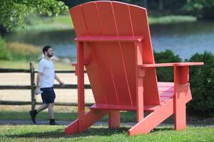An enormous pink adirondack chair sits by the walking path around Great Hollow Lake in Wolfe Park in Monroe, Conn. The Monroe Parks and Recreation Department has announced the schedule for the 2019 Summer Concert Series at Wolfe Park.