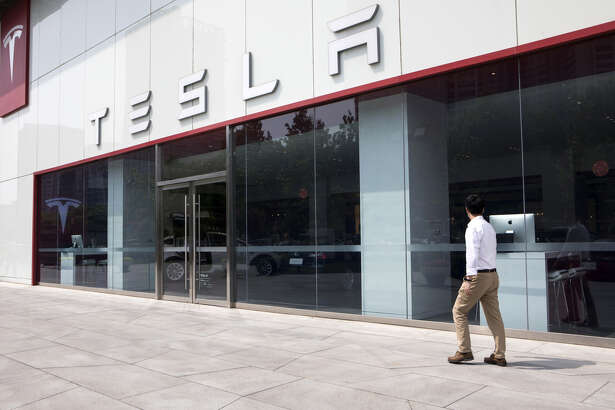 A pedestrian walks past a Tesla showroom.