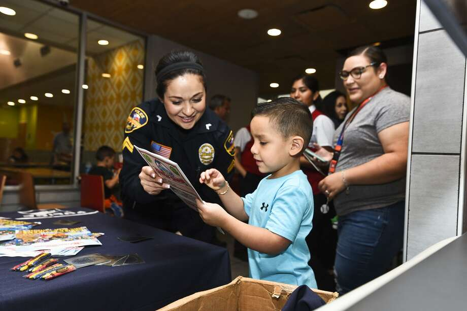 Laredo Police Department Investigator Gina Gonzales shows a book to young Lyam Tello on Saturday. Photo: Laredo Morning Times / Laredo Morning Times