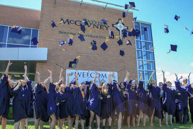 Graduates participate in the traditional cap toss after the ceremony at Father McGivney Catholic High School on Sunday afternoon. Graduates and families have lunch prior to the graduation ceremony.